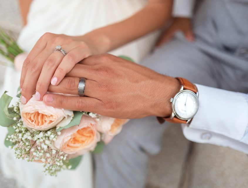 Couple holding hands with wedding rings over flowers