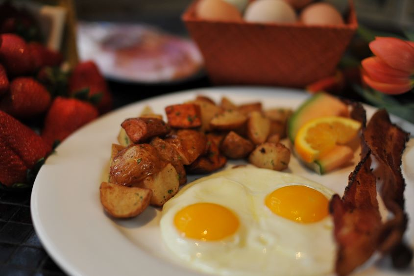 Close up of a plate of eggs, bacon, potatoes, and fruit for breakfast at Andaluca Restaurant.