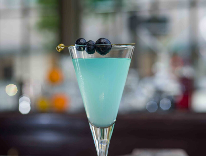 blue cocktail with blueberry garnish