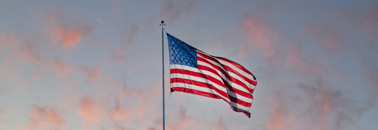 american flag in front of a sunset