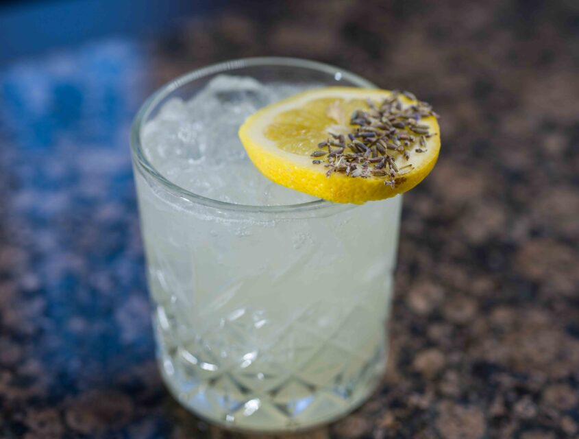 Cocktail topped with lemon slice and caraway seeds at our downtown cocktail bar in Seattle.