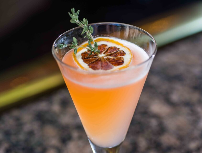 An orange cocktail topped with a candied orange slice and thyme at our cocktail bar in Seattle.