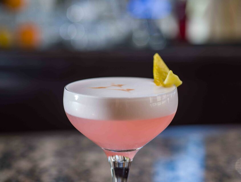 Close up of a frothy pink cocktail topped with a lemon rind at Oliver's Lounge in Seattle.