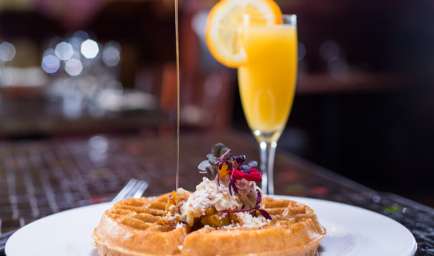 a mimosa and syrup being poured onto a waffle