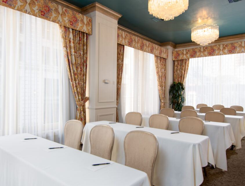 Five rows of tables with white tablecloth and chandeliers overhead in one of our Seattle event spaces.