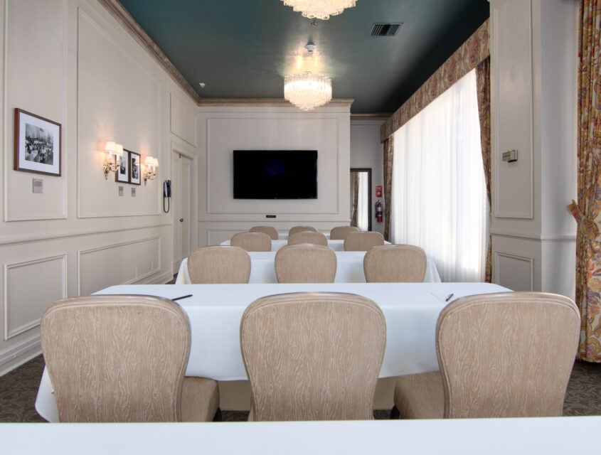 Four rows of tables with white tablecloth in the Rose Room, one of our Seattle event spaces.
