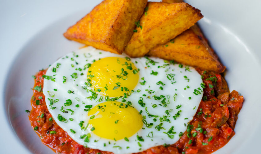 two fried eggs over a red sauce with toast